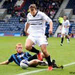 Greig avoids a robust tackle