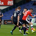 Barr looks on as McManus is surrounded by the Ross County defence.